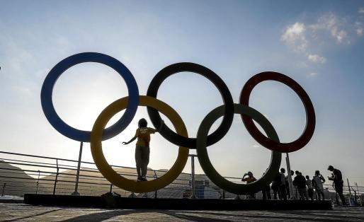 Una persona posa sobre los anillos dentro de la villa olímpica de Río de Janeiro.