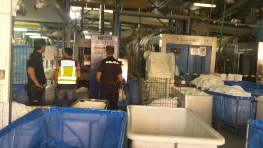 Agentes de la Policía Nacional realizan un registro en la lavandería Alfesa durante la investigación de un presunto caso de explotación laboral.