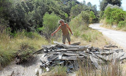Bernat Fiol, de GADMA, ante una parte de los restos de uralita arrojados en la Serra.