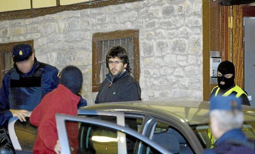 Uno de los detenidos es introducido en el vehículo policial tras el registro de su vivienda en Vitoria.