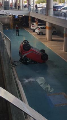 Imagen del coche rojo que se ha caído desde la zona de Urgencias hasta el aparcamiento de abajo.