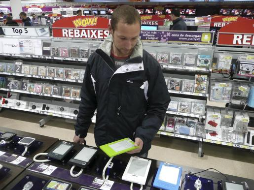 Un cliente observa los diferentes modelos de ebook disponibles en una tienda de Palma.