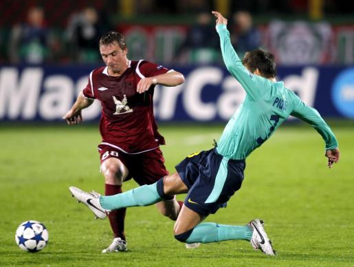 El jugador del FC Rubin Kazan, Sergei Kornilenko (dcha), pelea por el control del balón con el defensa del FC Barcelona, Gerard Piqué, durante el partido del grupo D de la Liga de Campeones disputado en Kazan, Rusia, el 29 de septiembre de 2010.