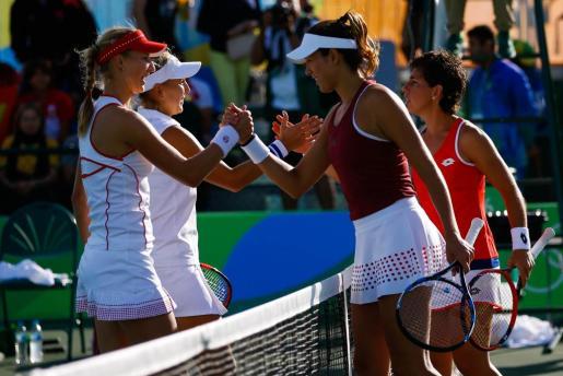 Las tenistas españolas Carla Suárez (d) y su compatriota Garbiñe Muguruza (2d), estrechan la mano de las rusas Ekaterina Makarova (i) y Elena Vesnina (2i) tras el partido de dobles en los cuartos de final.