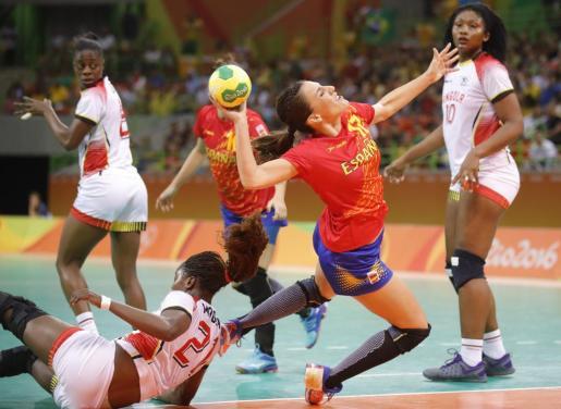 La jugadora española Elisabeth Pinedo (c), lanza tras superar a Magna Kazagna (abajo) de Angola.