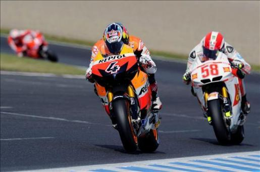 El piloto italiano de MotoGP del equipo Repsol Honda, Andrea Dovizioso, seguido por el italiano Marco Simoncelli (dcha), durante la clasificación oficial del Gran Premio de Japón .