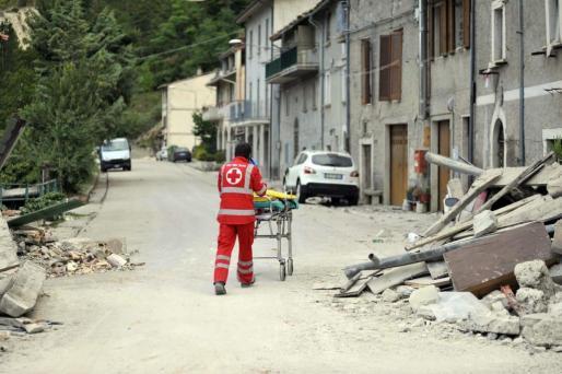 Un trabajador de la Cruz Roja italiana lleva una camilla delante de los escombros de un edificio en Pescara del Tronto.
