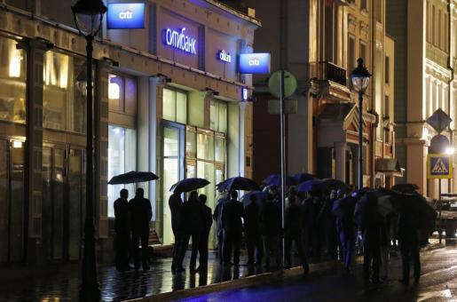Oficiales de policía y miembros de los servicios de seguridad esperan frente a una sucursal del banco Citibank en la capital rusa tomada por un asaltante.