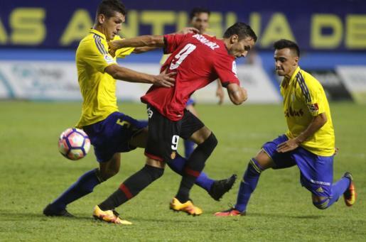 Óscar Díaz, autor del gol del Real Mallorca, intenta deshacerse de los jugadores del Cádiz para recibir un balón.