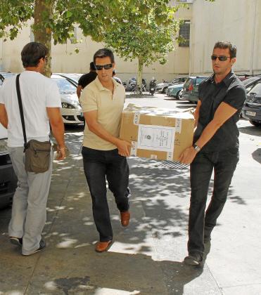 Dos policías trasladan documentación del 'caso Ibatur'.