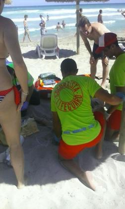 Los socorristas atienden a una de las dos personas rescatadas este martes en la playa de Can Picafort.