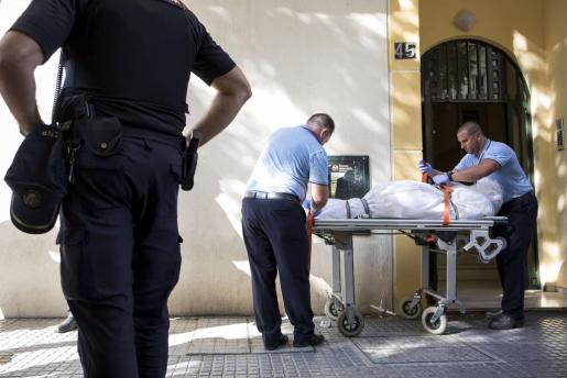 Empleados de la funeraria trasladan uno de los tres cuerpos que han sido hallados sin vida en una vivienda de la barriada malagueña de El Palo.