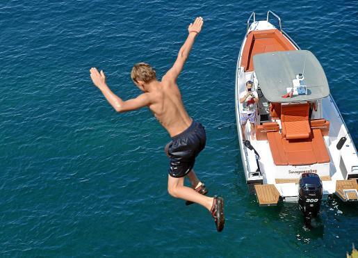 Uno de los niños británicos saltando mientras su padre desde la barca lo graba con el móvil.