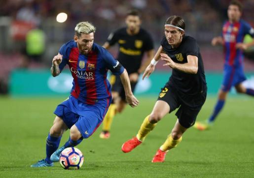 El delantero argentino del F. C. Barcelona, Leo Messi, se lleva el balón ante el defensa brasileño del Atlético de Madrid, Filipe Luis.