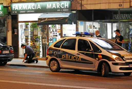 Agentes del Cuerpo Nacional de Policía en la farmacia que fue asaltada, sita en la calle Joan Miró. Fotos: VASIL VASILEV