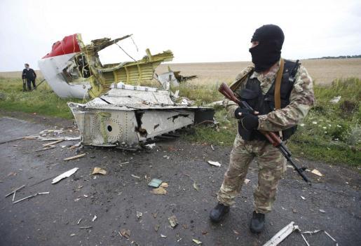 Un miliciano prorruso junto a uno de los restos del aparato que cayó en un punto de la región separatista de Donetsk, en Ucrania.