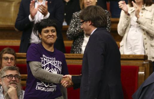 El presidente de la Generalitat, Carles Puigdemont, saluda a la diputada de la CUP Anna Gabriel, tras superar la cuestión de confianza planteada ante el Parlament con los votos independentistas de Junts pel Sí (JxSí) y la CUP.