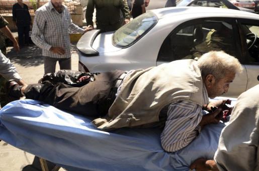 Fotografía facilitada por la Agencia de Noticias siria (SANA) que muestra a un hombre herido a quien trasladan al hospital en Alepo.