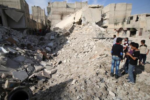 Un grupo de gente inspecciona las ruinas dejadas por las bombas en un feudo rebelde de Alepo.