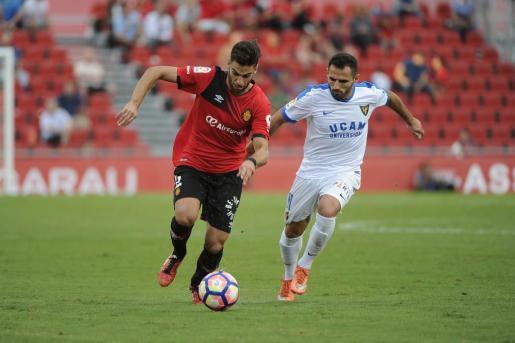 Company conduce el balón ante un jugador del UCAM Murcia.