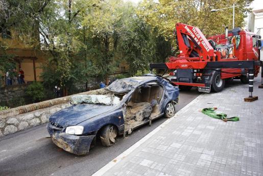 Una grúa retira el vehículo del hombre que falleció al ser arrastrado por el agua en una riera de Vilassar de Mar (Barcelona), como consecuencia de las lluvias torrenciales que cayeron por la tarde en la comarca barcelonesa del Maresme.