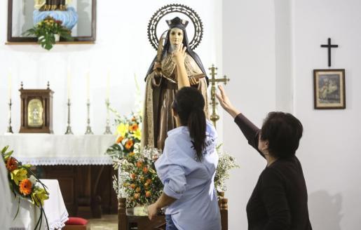 Unas vecinas de Es Cubells mostrando su afecto y cariño a la venerada imagen de Santa Teresa. Foto: ARGUIÑE ESCANDÓN
