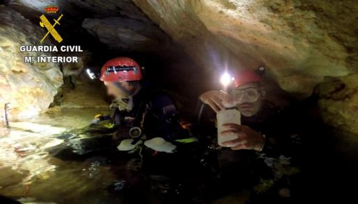 Agentes del Geas recogiendo muestras de agua en la cueva de Vallgornera.