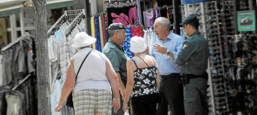 Dos agentes de la Guardia Civil conversan con un comerciante en presencia de dos turistas en Magaluf.