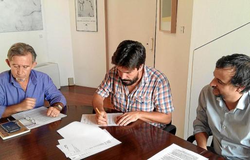 Gómez de la Cuesta, firmando su contrato entre Miquel Perelló, entonces concejal del Cultura, y Llorenç Carrió, quien le sucedió en el cargo y quien tomó la decisión de la destitución.