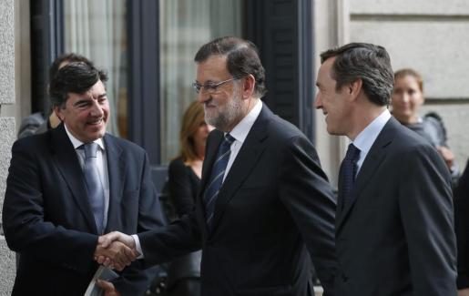 El presidente del Gobierno en funciones y candidato del PP, Mariano Rajoy (c), junto al portavoz parlamentario del partido, Rafael Hernando (d), saluda al diputado popular José Bermúdez de Castro (i), a su llegada al Congreso para asistir al debate de su investidura.