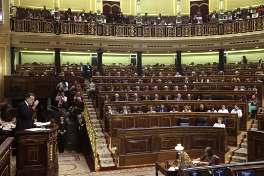 El presidente del Gobierno en funciones, Mariano Rajoy (i), responde a la intervención del portavoz del PSOE, Antonio Hernando, durante la segunda jornada del debate de su investidura.