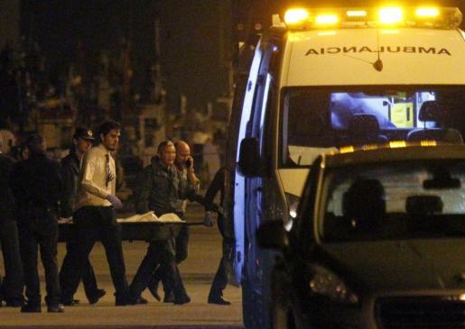 Agentes de la Guardia Civil y de los servicios funerarios trasladan los restos mortales de una de las cuatro personas que han fallecido en la persecución.
