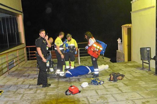 Los sanitarios del 061 y un agente de la Policía Local, junto al cadáver del ciudadano alemán.