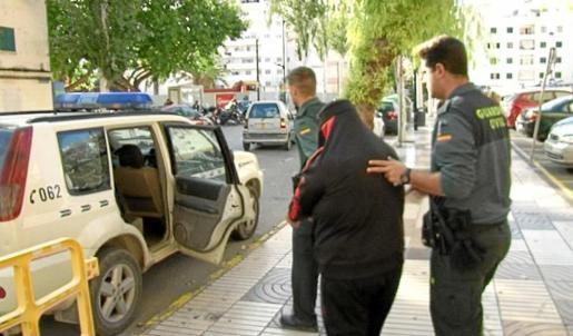 Agentes de la Guardia Civil custodian al detenido que abandonó los juzgados esposado y cubriéndose la cara con la chaqueta. Foto: TEF