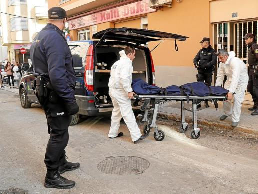 Trabajadores de la empresa fúnebre, retirando el cadáver de la mujer asesinada.