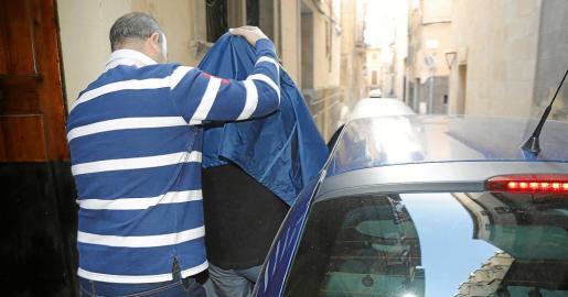El detenido, que se cubrió la cabeza con una chaqueta, es introducido en el vehículo policial ayer tras el registro en su casa de la calle Calders.