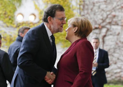 Mariano Rajoy y Angela Merkel se saludan antes de participar en una cumbre de líderes europeos con el presidente Barack Obama.