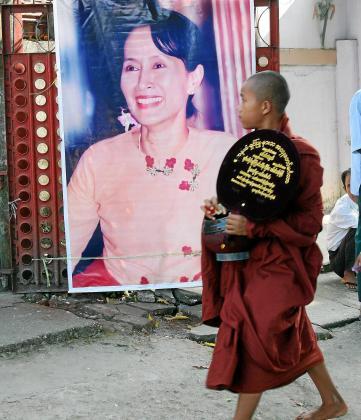Un monje observa una imagen de la líder de la Liga Nacional por la Democracia. Foto:EFE