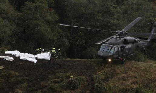 Miembros de los organismos de rescate transportan los cuerpos del avión accidentado.
