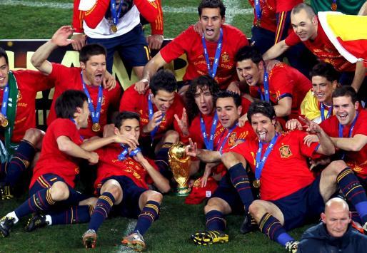 Los jugadores de la selección española posan con la copa del mundo en el cesped del Soccer City después de que el equipo español consiguiera vencer en la final del Mundial de Sudáfrica a la selección de Holanda por 1-0.