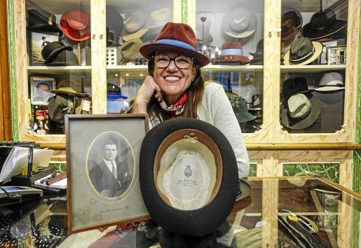 Virginia Bonet, que es la tercera generación de la familia, posa con el retrato de su abuelo y un sombrero que él mismo hizo para un cliente de la época.