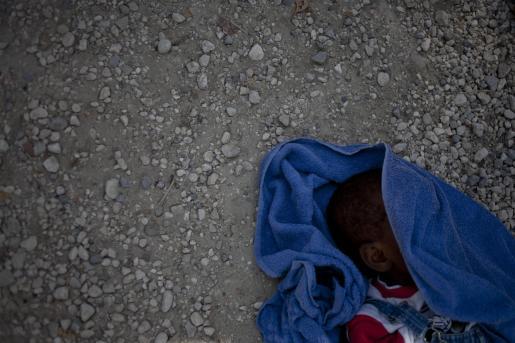Un bebé muerto por cólera yace en el suelo en la entrada del hospital de Arcahie en la provinicia de Artibonite.