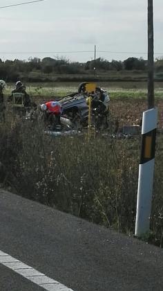 Imagen del coche volcado en un campo cercano a la carrtera.