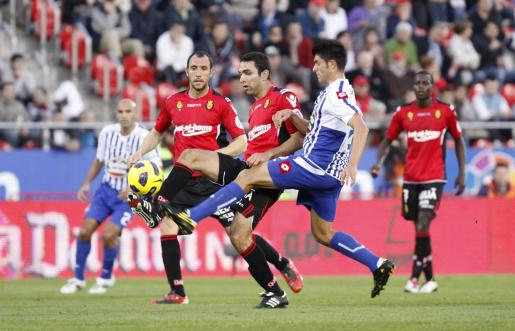 Joao Victor toca el balón en presencia de Ramis y acosado por Rubén, durante el partido de ayer en Son Moix.