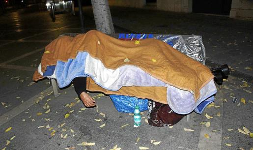 Un hombre sin hogar descansa en un banco de la calle.