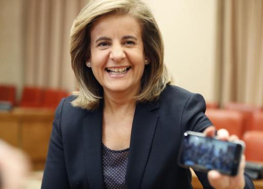 La ministra de Empleo, Fátima Báñez, muestra la foto que ha hecho con su teléfono móvil a los fotógrafos, antes de su comparecencia en la Comisión de Empleo y Seguridad Social, en el Congreso de los Diputados.