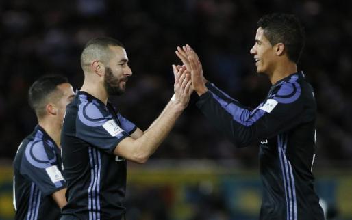 El delantero francés del Real Madrid Karim Benzema celebra el primer gol de su equipo junto a su compañero de selección Raphael Varane.