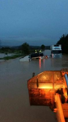 Imagen de la carretera de Campos a Porreres, cortada por las inundaciones. Agentes de la Guardia Civil, sobre el techo del frugón.