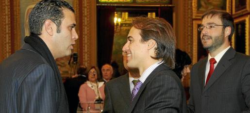 Palmer habla con Gijón y Veramendi, mientras Hila intenta introducirse en la conversación.