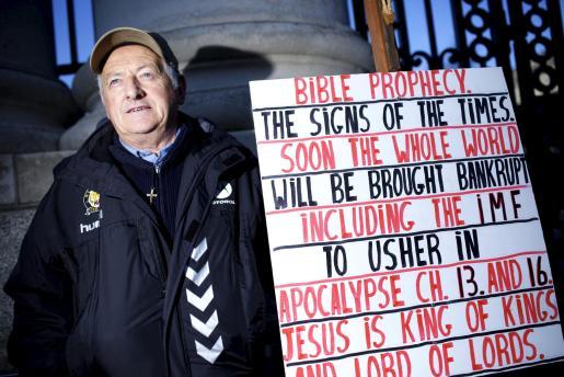 Un manifestante que cree que la crisis de su país estaba anunciada en la biblia, protesta afuera de la sede del gobierno irlandés en Dublín.